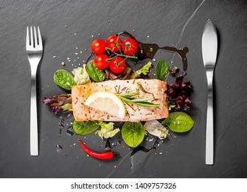 Grilled salmon fillet with salad on black slate plate