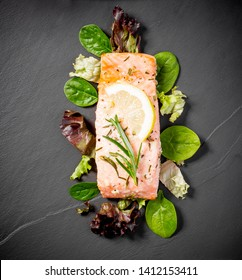 Grilled salmon fillet with salad on black slate plate, top view