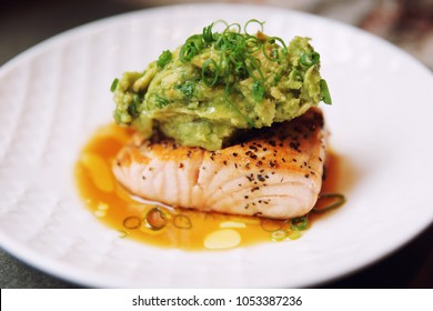 Grilled salmon fillet topped with avocado mash, leek and crushed nuts, cross-processing tone