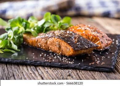 Grilled salmon fillets sesame seeds herb decoration and black slate board on old oak table.