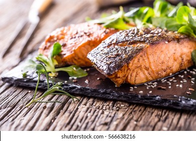Grilled salmon fillets sesame seeds herb decoration and black slate board on old oak table.