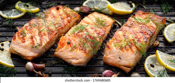 Grilled salmon fillets sprinkled with fresh herbs on a grill plate close up