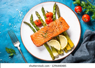 Grilled salmon fish fillet with asparagus and tomato. Top view on blue stone table.