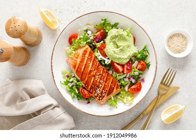 Grilled salmon fish fillet and fresh green lettuce vegetable tomato salad with avocado guacamole. Top view.