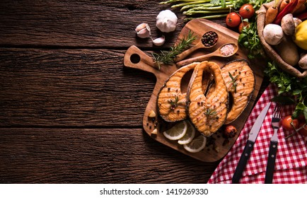 Grilled salmon fish with seasoning and various vegetables on cutting board on old wooden background