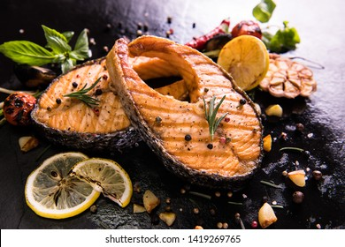 Grilled salmon fish with seasoning and various vegetables on cast Iron pan background