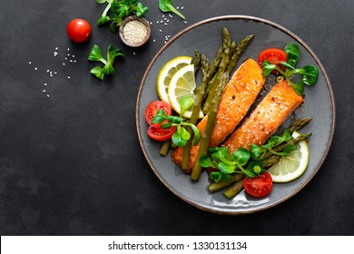 Grilled salmon fish steak, asparagus, tomato and corn salad on plate. Healthy dish for lunch. Top view