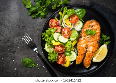 Grilled salmon fish steak with fresh vegetables salad on black stone table. Keto diet food. Top view with copy space.
