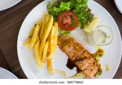 Grilled salmon with home made dipping sauce and french fries