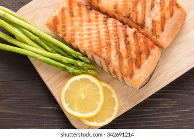 Grilled salmon and lemon, asparagus, on the wooden table.