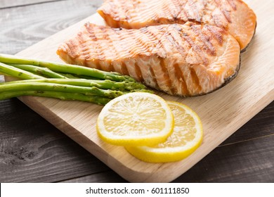 Grilled salmon with lemon, asparagus on the wooden table.