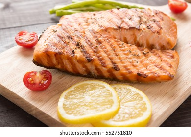 Grilled salmon and lemon, asparagus, tomato on the wooden table.