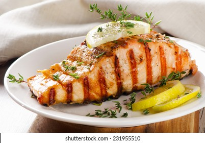 Grilled Salmon with lemon, olives and fresh thyme. Selective focus