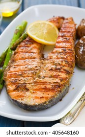 grilled salmon with lemon and vegetables on white dish