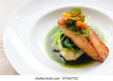Grilled salmon with mashed potato and spinach with an edible flower salad.