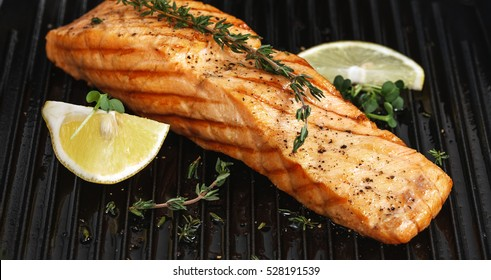 Grilled salmon on grill closeup with lemon and thyme