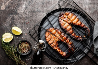 Grilled salmon on iron grill grate on a dark background top view. BBQ seafood. spece for a text