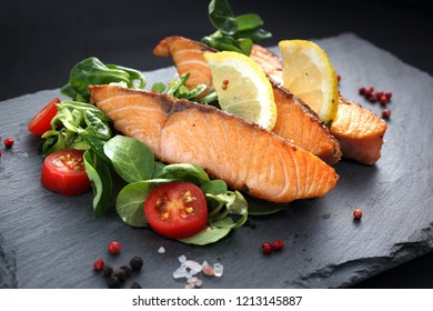 Grilled salmon on lettuce. Dinner dish on a black plate.
