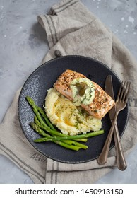 Grilled salmon portion with smashed potatoes and green asparagus.