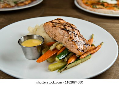 Grilled Salmon with potatoes and vegetables on white plate