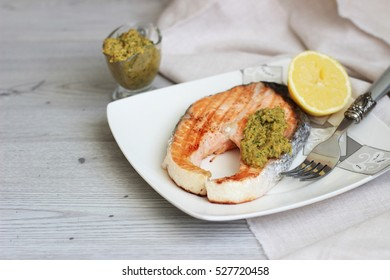 Grilled salmon with sauce and lemon on wooden background