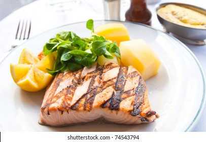 grilled salmon with sauce,lemon and tomato