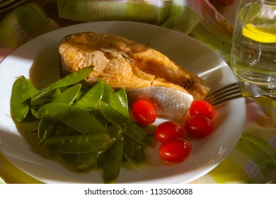 Grilled salmon served tomatoes. Glass of water with lemon