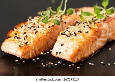 Grilled salmon, sesame seeds  and marjoram on a black plate. Studio shot