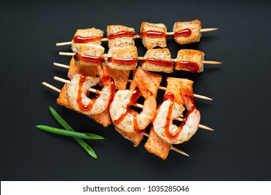 Grilled salmon, shrimps and pork on skewers top view on a black background.  Small kebab  grilled seafood and meat on skewers .