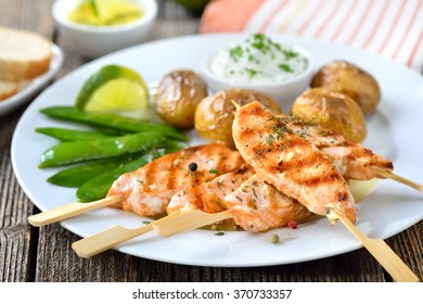 Grilled salmon skewers served with snow peas and baked potatoes with sour cream