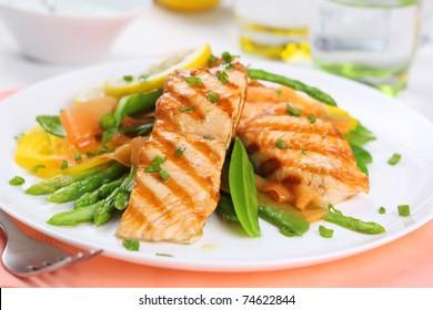 gegrillter Lachs mit Frühlingsgemüse auf weißem Teller, weicher Fokus