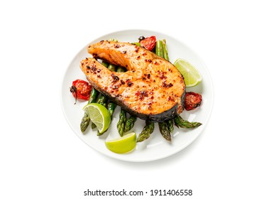 Grilled salmon steak with asparagus and tomatoes cherry on a white  plate isolated on white  background
