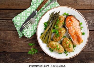 Grilled salmon steak and baked new potato with asparagus on wooden background, top view