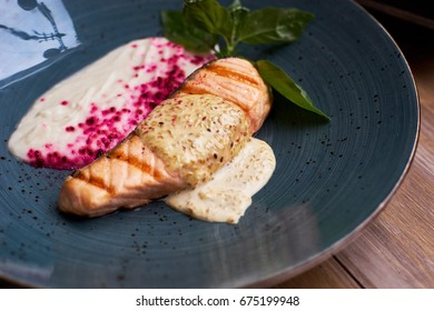 Grilled salmon steak with cauliflower cream and sesame creamy sauce on blue ceramic plate on wooden table