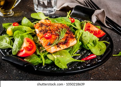 Grilled salmon steak filet with fresh vegetables, spinach and lime, dark rusty table copy space