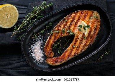Grilled salmon steak with fresh thyme, lemon and pink salt, top view