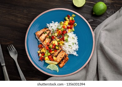 Grilled salmon steak with fruit sauce and rice on a blue plate. Delicious meal made of fish and exotic fruits and vegetables on a table. Top view shot above.
