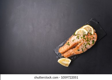 Grilled salmon steak on a dark black background with lemon and herbs. Seafood restaurant concept. Copy space