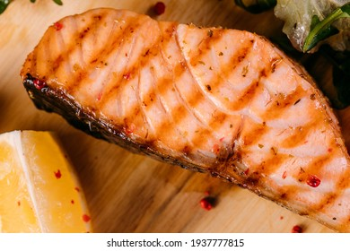 Grilled salmon steak on a wooden board with a fresh healthy salad, lemon, vegetables, herbs and spices on a dark concrete background.