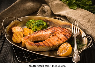Grilled salmon steak with potatoes, broccoli, lemon and herbs in old roasted metal plate on a wooden table rustic stile