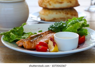 Grilled salmon steak with sauce and salad leaves