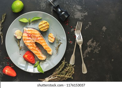 Grilled salmon steak served on a gray plate, black concrete background. Top view,flat lay.