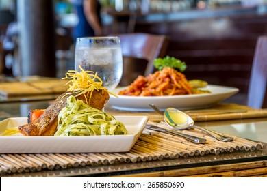 gegrilltes Lachssteak mit Nudeln und Gemüse in einem kleinen Restaurant im Freien