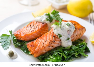 Grilled Salmon Steak  with Spinach, Tartare Cream and Lemon Wedges