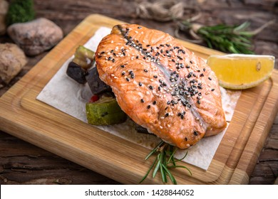 Grilled salmon steak with vegetables on wooden table. Beautiful stylish menu. Free space for text