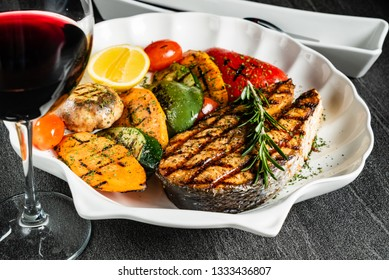 Grilled salmon steak with grilled vegetables and red wine