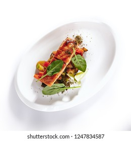 Grilled Salmon Steak with Warm Vegetable Salad Isolated on White Background. Restaurant Main Course with Barbecue Red Fish or Trout Fillet, Greens, Black Pepper and Lime Top View