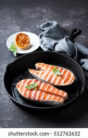 Grilled salmon steaks in cast iron pan, selective focus