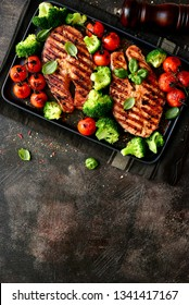 Grilled salmon steaks with vegetables on a black plate over dark slate, stone or concrete background.Top view with copy space.