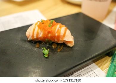 Grilled salmon sushi, Janapanese food on black plate